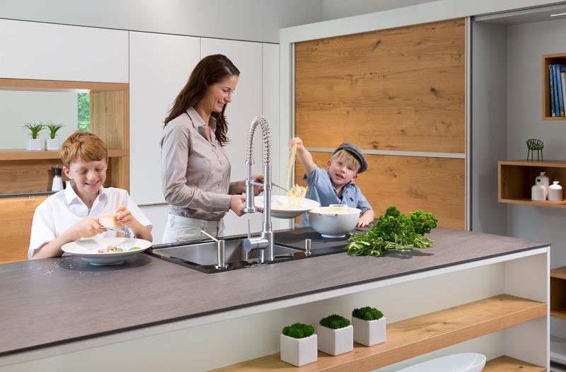 Mutter mit ihren zwei Söhnen kocht Spaghetti in Rempp Küche